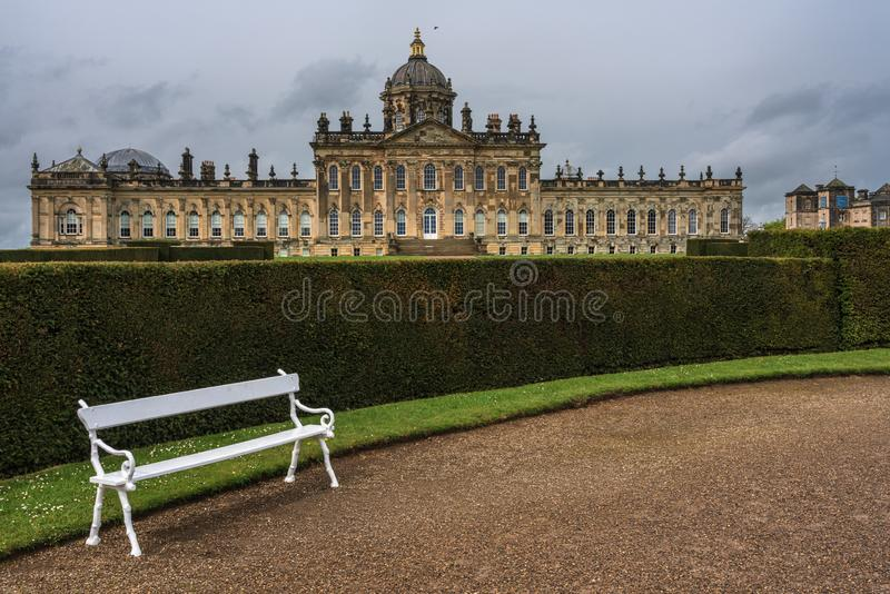 Part of the garden of Castle Howard, with a white bench and the. Castle Howard, North Yorkshire, United Kingdom - May 7, 2019 :  Part of the garden of Castle royalty free stock photos