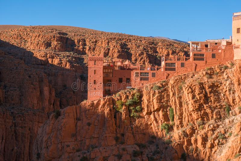 Castle kasbah hotel on the high Cliff in amazing place at Picturesque Serpentine mountain road in Gorges Dades in high. Atlas, Morocco stock photo