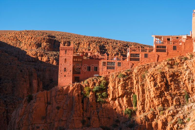 Castle kasbah hotel on the high Cliff in amazing place at Picturesque Serpentine mountain road in Gorges Dades in high. Atlas, Morocco stock images