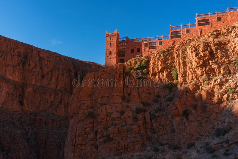 Castle kasbah hotel on the high Cliff in amazing place at Picturesque Serpentine mountain road in Gorges Dades in high. Atlas, Morocco royalty free stock photos