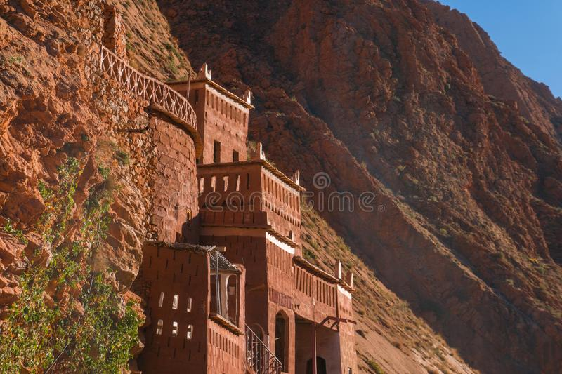 Castle kasbah hotel on the high Cliff in amazing place at Picturesque Serpentine mountain road in Gorges Dades in high. Atlas, Morocco stock photos