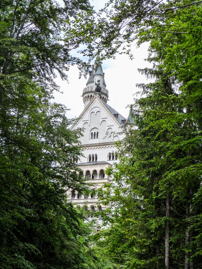 Castle of Neuschwanstein in Germany near Munich, Bavaria. Main tower trough trees. royalty free stock images