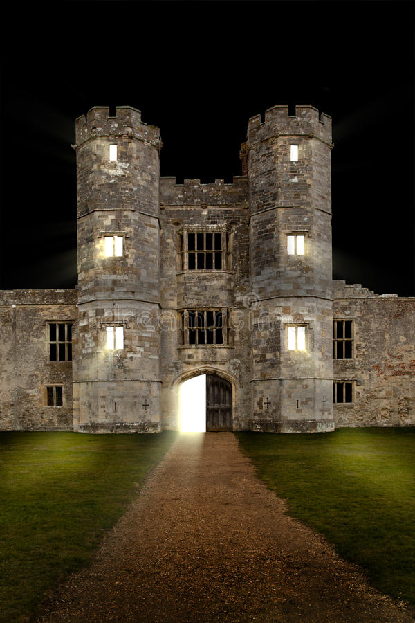 Castle at night with door opening. And lights shining through stock photos