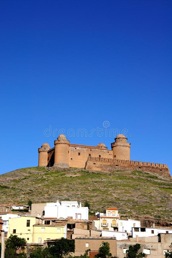 Castle overlooking the town, La Calahorra, Spain. View of the castle on the hilltop with town buildings in the foreground, La Calahorra, Granada Province stock photo