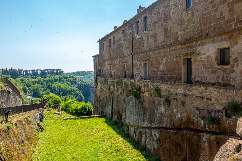 The castle rocks of little medieval city of Sorano, Tuscany, Italy, with hills and blue sky in background royalty free stock image