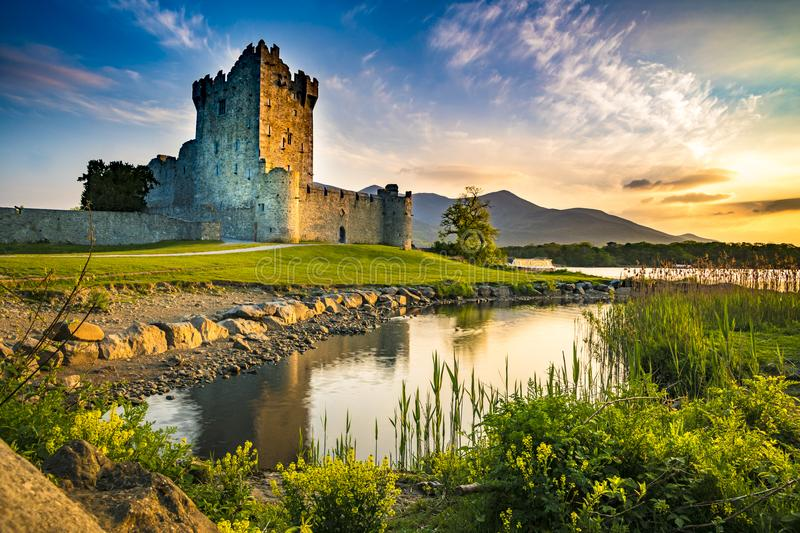 Castle ruin with a lake and grass at the sunset orange sky. Ancient old Fortress Ross Castle ruin with lake and grass in Ireland during golden hour nobody stock photo