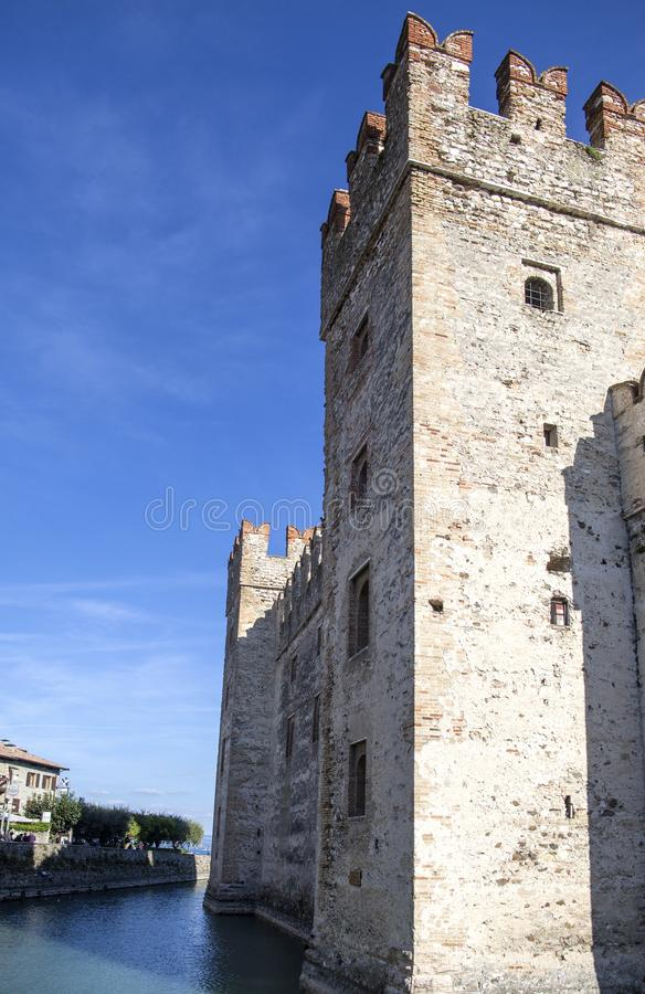 Castle in Sirmione - October 2, 2018: View to the medieval Rocca Scaligera castle 13th century in Sirmione town on Garda lake. Near Verona, Italy. Access point stock image