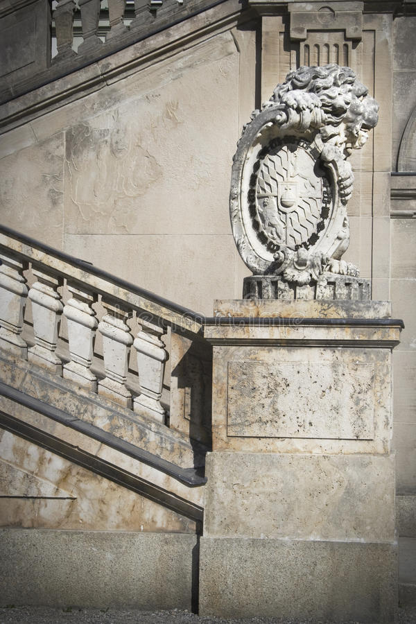 Castle staircase detail. Detail of the Nymphenburg castle enterance stairs in Munich, decoration with a stone lion holding bavarian symbols stock photography