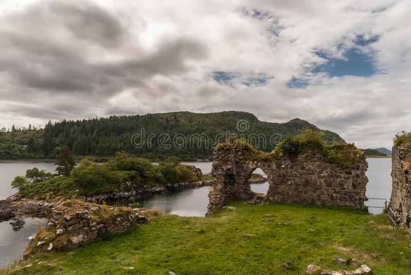 Castle Strome ruins with Loch Carron, Scotland. Stromeferry, Scotland - June 10, 2012: Castle Strome ruins on green hill. Green weeds on walls. Gray Loch Carron stock photo