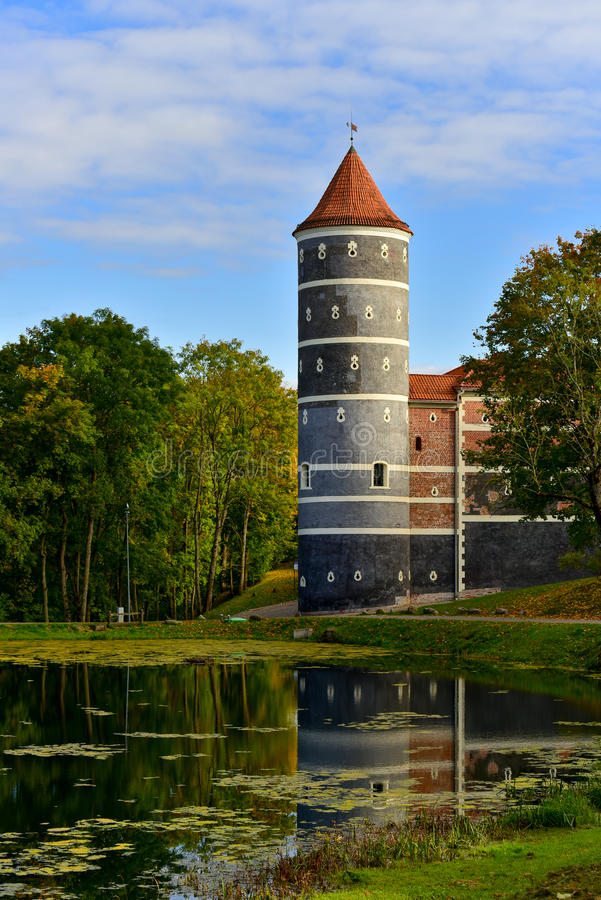 Castle tower Lithuania. View of Panemune castle tower in Lithuania in early autumn park surroundings, water reflection royalty free stock photo