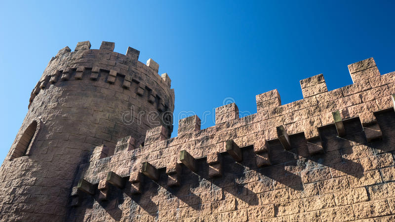 Castle tower and walls. A castle tower and walls made of bricks and with the blue sky in the background royalty free stock photography