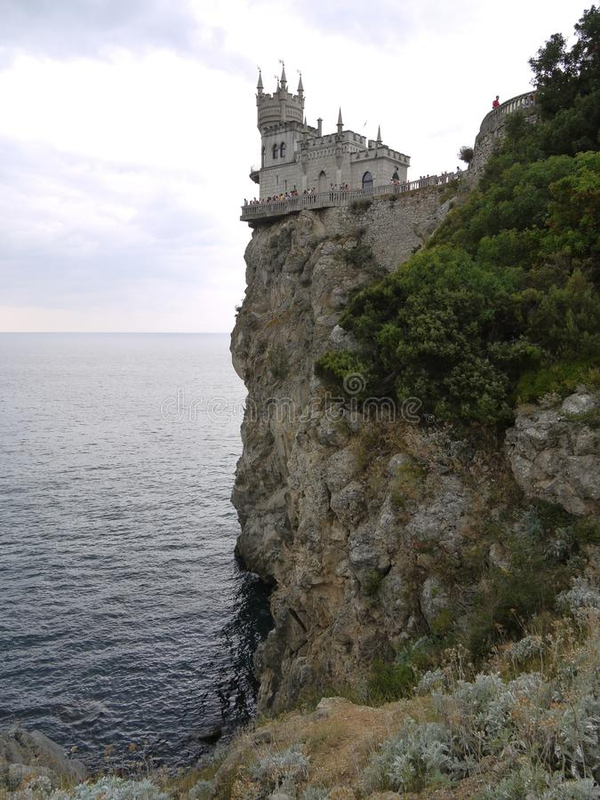 A castle with turrets located at the very edge of a cliff standing in the sea. With fences around the edges and tourists. Looking at local beauty from a bird`s royalty free stock images