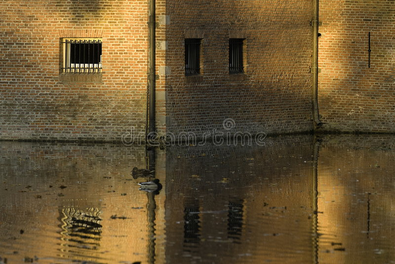Castle Wall. Part of a castle wall standing in the water during in the afternoon royalty free stock photo