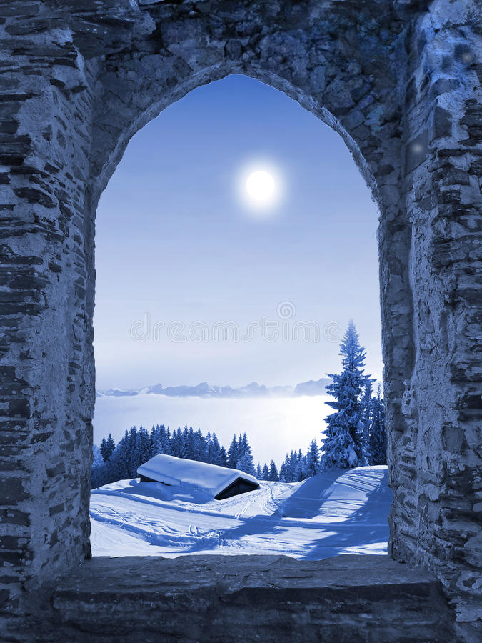 Castle window with moonlight scenery. View through ancient castle window to winter landscape in the austrian mountains, imaginary moonlight scenery in shades of stock photos