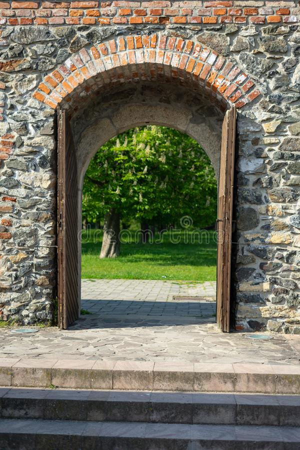 Castle wooden door leading to garden. Of the castle royalty free stock photos