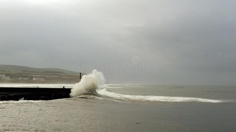 Castlerock Northern Ireland. Beautiful ocean wave breaking on the wharf and the lighthouse royalty free stock images