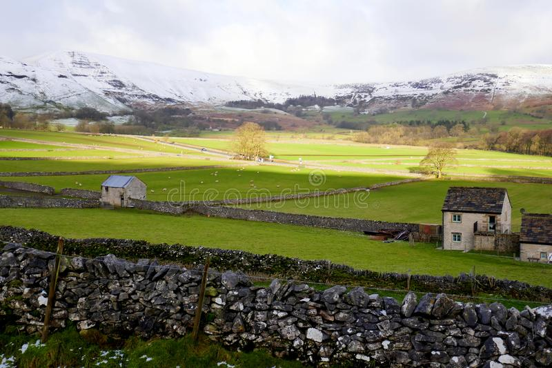Castleton, Derbyshire, UK. February 01, 2018. Farmland sheltered in the Hope valley by the mountains of MamTor and the Great Ridge which are covered in Snow at stock photos