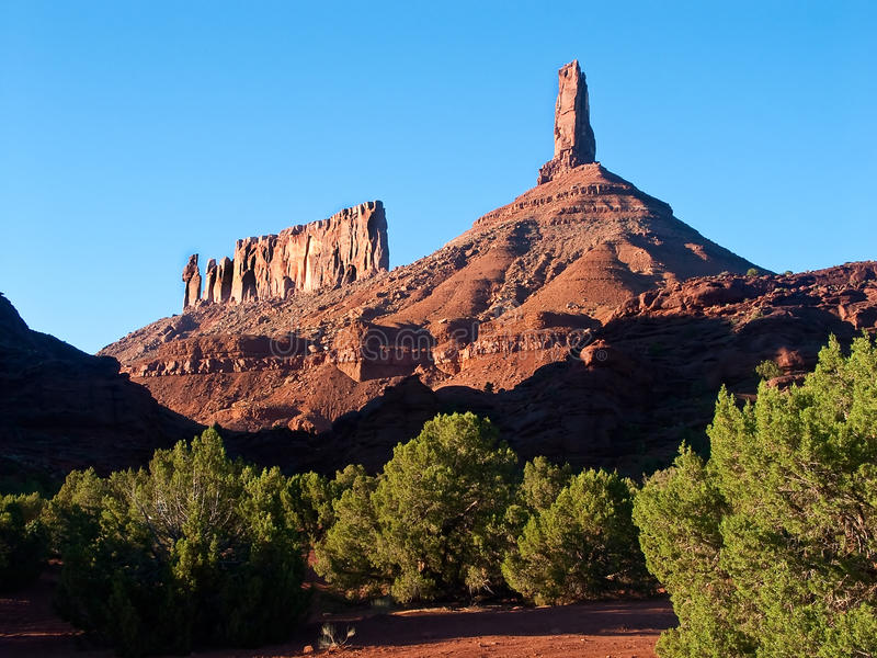 Castleton Tower and. Castleton Tower (right) and the Priest, Nuns and Rectory (left) rise dramatically from the floor of the Castle Valley near Moab, Utah, an stock photography