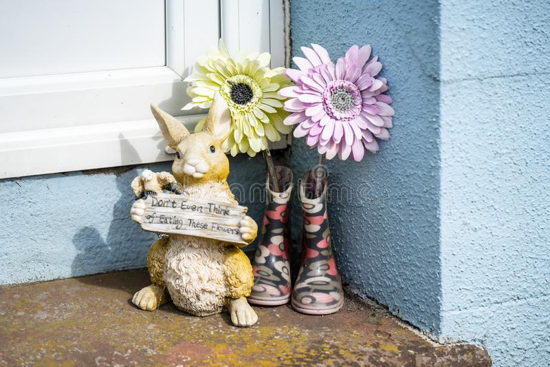 Castletown, Isle of Man, am 16. Juni 2019 Bunny Rabbit Home oder Garten-Tierfigürchen, Statue, Blumen und ein Paar wellingtons lizenzfreies stockbild