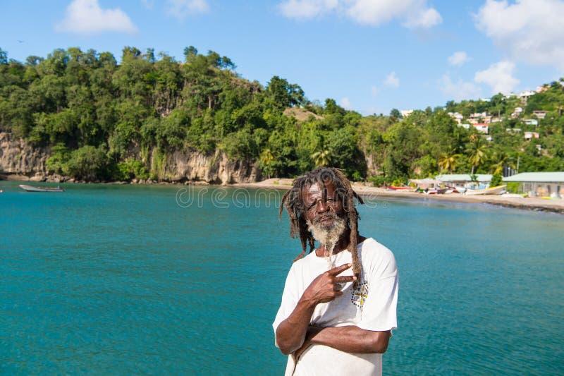 Castries, stLucia - 26 de novembro de 2015: vitória da mostra do homem ou gesto africano da paz no mar azul Homem desabrigado ido imagem de stock royalty free