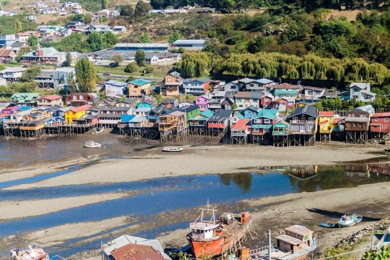 CASTRO, CHILE - 23 DE MARZO DE 2015: Barcos de pesca y casas del zanco de los palafitos durante marea baja en Castro, isla de Chi imagen de archivo