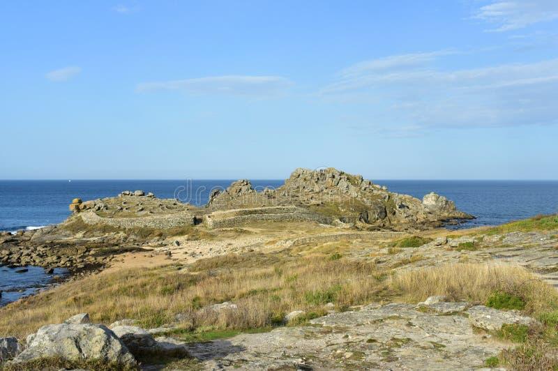 Castro de Barona, Galicia, España Ruinas prehistóricas y playa del acuerdo con las rocas Mar azul, día soleado foto de archivo libre de regalías