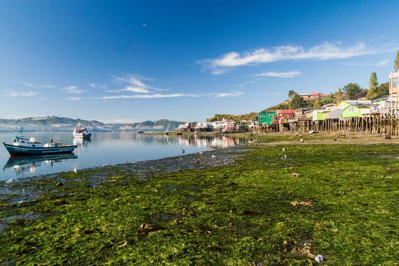 CASTRO, O CHILE - 23 DE MARÇO DE 2015: Barcos de pesca e casas do pernas de pau dos palafitos durante a maré baixa em Castro, ilh fotografia de stock royalty free