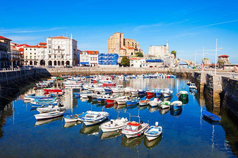 Castro Urdiales city in Spain. Boats at the port of Castro Urdiales, Santa Maria Church and Santa Ana Castle Lighthouse in Cantabria region in northern Spain stock photography