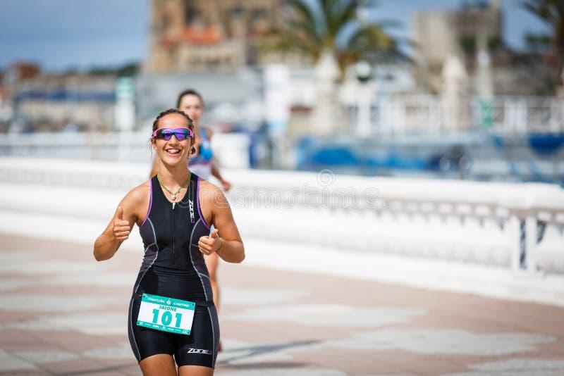 CASTRO-URDIALES, ESPAÑA - 17 DE SEPTIEMBRE: La mujer no identificada del triathlete en la competencia corriente celebró en el tri fotografía de archivo libre de regalías