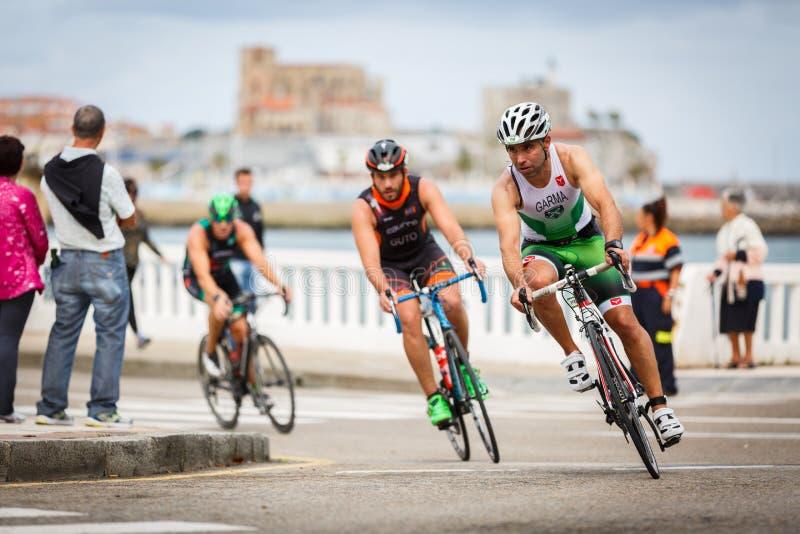 CASTRO URDIALES, ESPANHA - 17 DE SETEMBRO: O triathlete não identificado na competição do ciclismo comemorou no triathlon de Cast fotos de stock royalty free