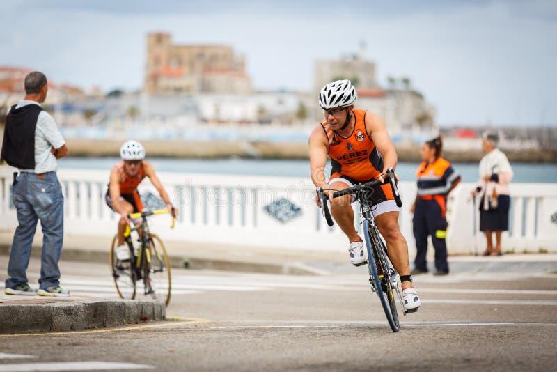 CASTRO URDIALES, ESPANHA - 17 DE SETEMBRO: O triathlete não identificado na competição do ciclismo comemorou no triathlon de Cast foto de stock royalty free