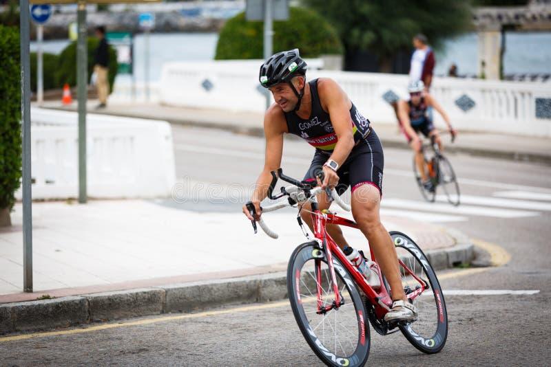 CASTRO URDIALES, ESPANHA - 17 DE SETEMBRO: O triathlete não identificado na competição do ciclismo comemorou no triathlon de Cast imagens de stock royalty free