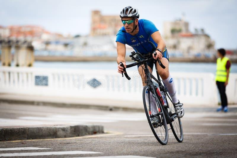 CASTRO URDIALES, ESPANHA - 17 DE SETEMBRO: O triathlete não identificado na competição do ciclismo comemorou no triathlon de Cast foto de stock
