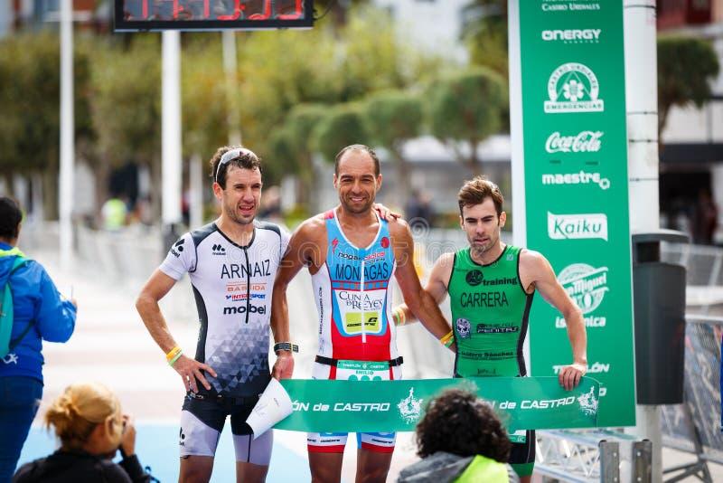 CASTRO URDIALES, ESPANHA - 17 DE SETEMBRO: O triathlete não identificado na extremidade da competição comemorou no triathlon de C imagem de stock