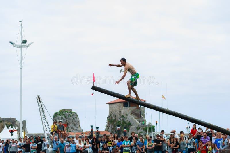 CASTRO URDIALES, SPANIEN - JUNI 29: Den oidentifierade pojken ankommer på flaggan i konkurrensen av den firade fetthaltiga polen  royaltyfri foto