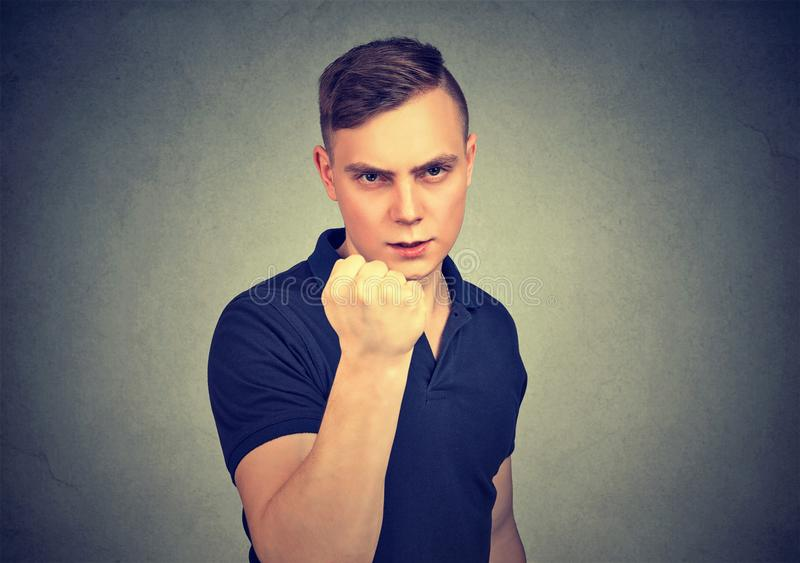 Aggressive young man threatening with fist hand stock photo