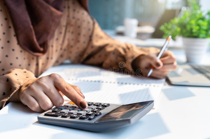 Casual accountant or banker woman hand using calculator at workplace royalty free stock image