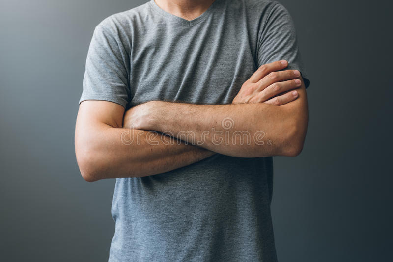 Casual adult man with arms crossed, body language. For stress relief, masking insecurities, anxiety and fear as well as self restraint or frustration stock images
