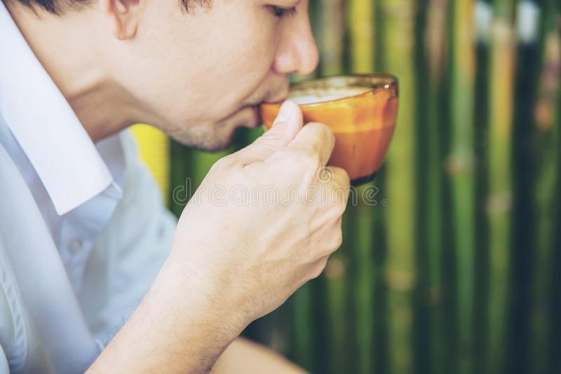 Casual Asian man drink hot coffee happily in nature royalty free stock photo
