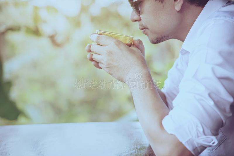 Casual Asian man drink hot coffee happily in nature stock photos