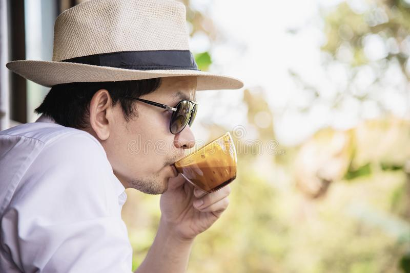 Casual Asian man drink hot coffee happily in nature royalty free stock photos