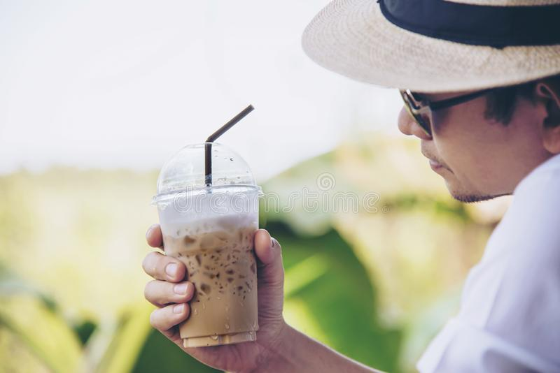 Casual Asian man drink ice coffee happily in nature royalty free stock photo