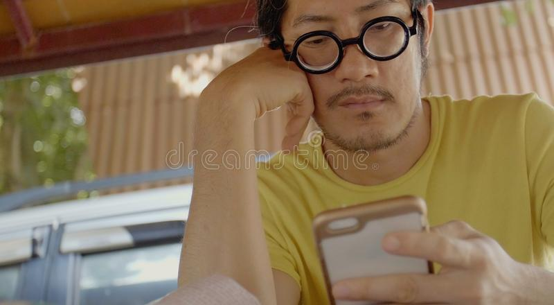 Casual asian man using smartphone .checking mails, chats royalty free stock photos