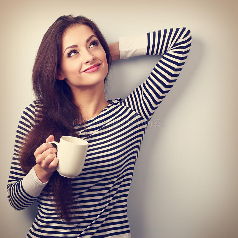 Casual attractive thinking woman holding cup of tea and pensive. Looking up. Vintage portrait royalty free stock photo