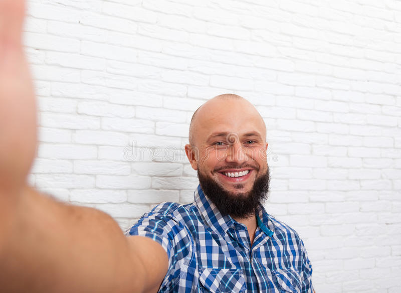 Casual Bearded Business Man Taking Selfie Photo. Office Over White Brick Wall royalty free stock photos