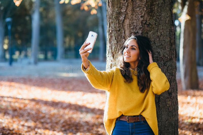 Young woman taking selfie photo with smart phone in autumn stock photos