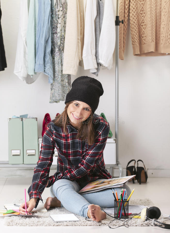 Casual blogger woman doing fashion sketches in her office. Young creative woman sitting in the floor with digital tablet stock images
