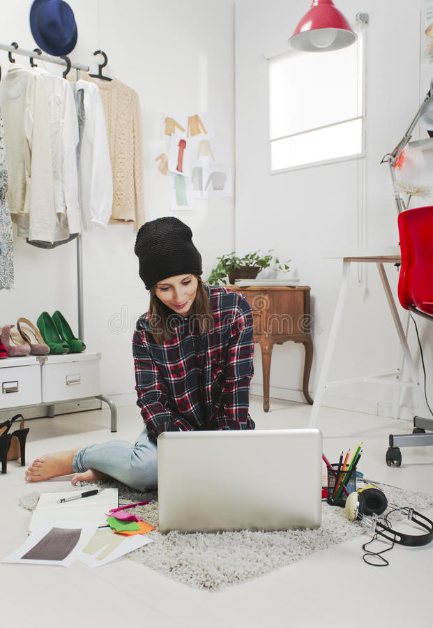 Casual blogger woman working in her fashion office. Young creative woman sitting in the floor with laptop stock image