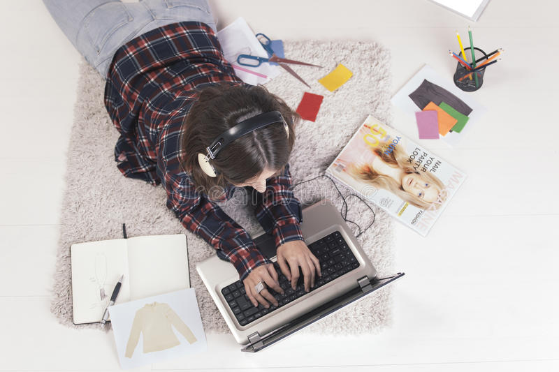 Casual blogger woman working with laptop in her fashion office. Young creative woman stretched in the floor and listening music stock image