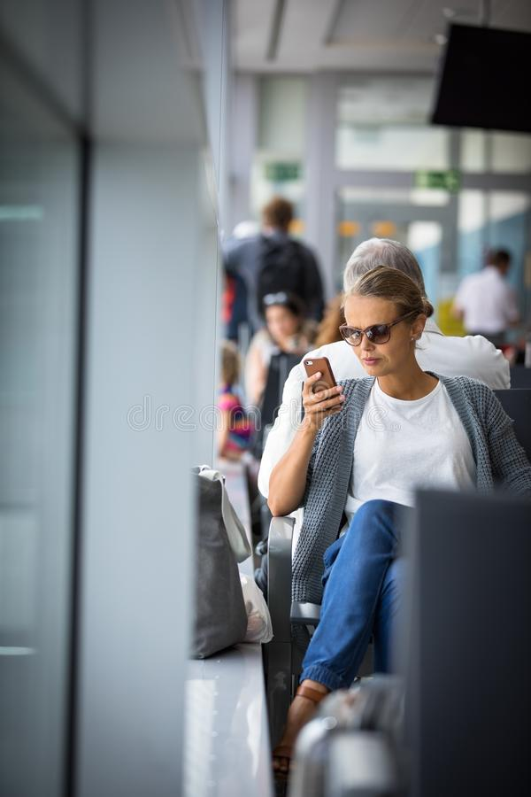 Young woman using her cell phone while waiting to board a plane at departure gates. Casual blond young woman using her cell phone while waiting to board a plane royalty free stock photos
